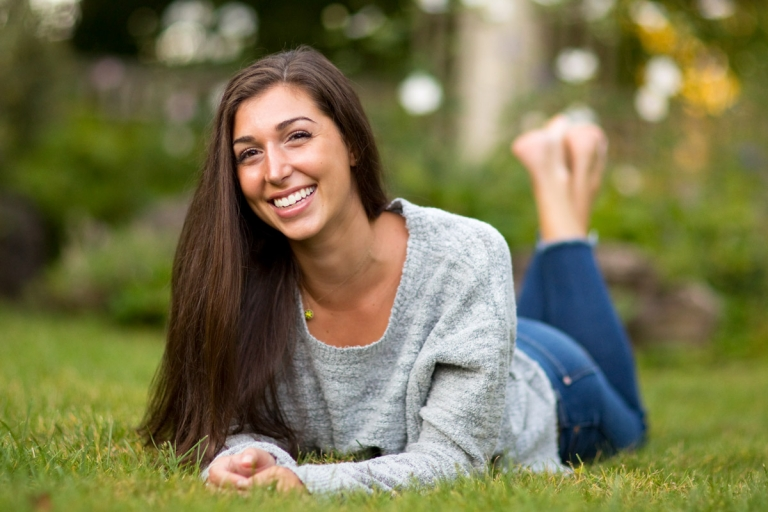 photo of a femail high school senior lying on the ground prone propped up by her elbows with feet in the air.