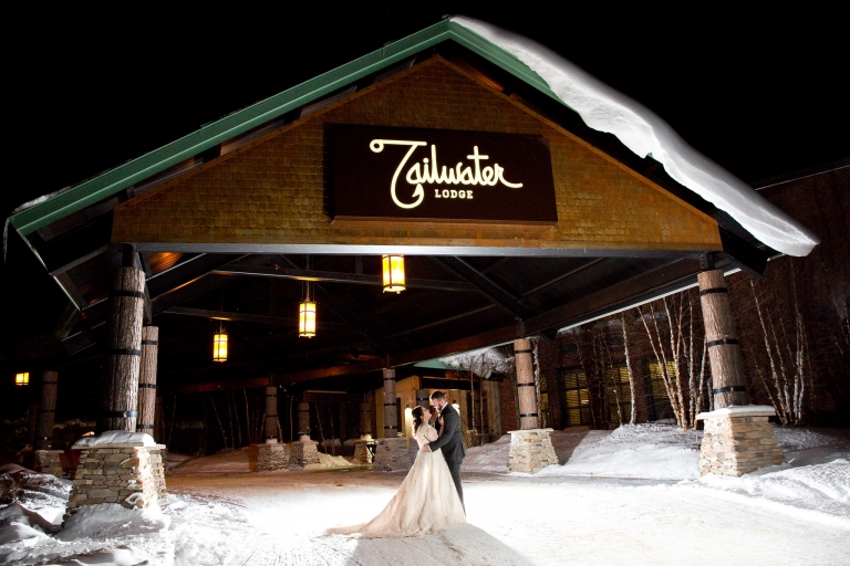 Photo of a bride and groom in an embrace outside the entrance of Tailwater lodge in a winter sub zero setting.