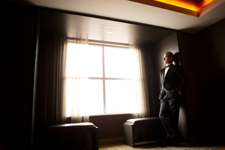 Photo of a groom, a full standing body portrait, lighted by a window.