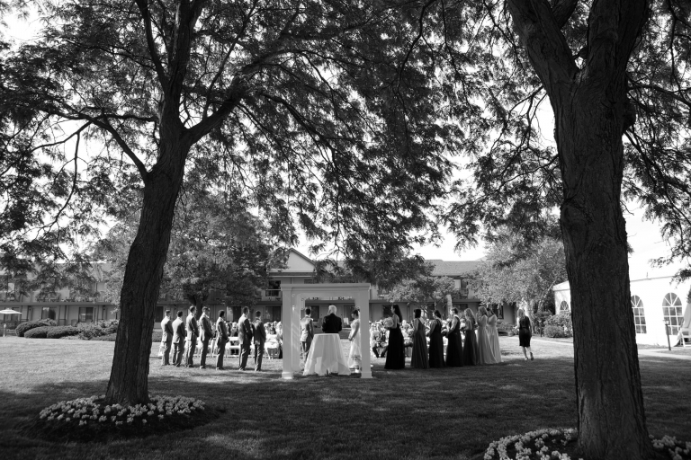 Photo of a wedding ceremony captured wide angle and from behind the ceremony, framed by two large trees.