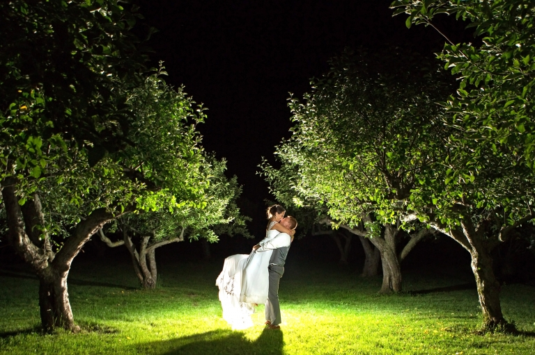 Photo of a groom lifting his bride in the middle of a apple orchard in this night shot.