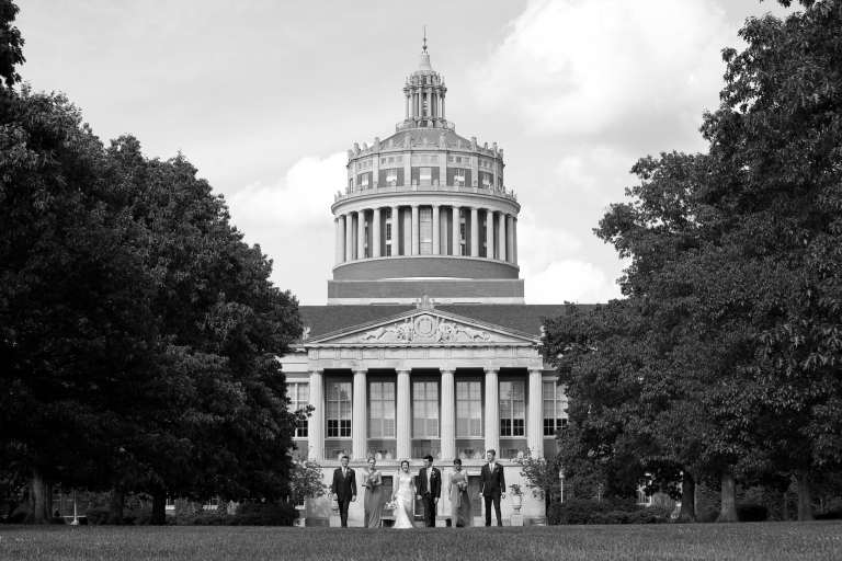 Photo of a small wedding party walking toward the camera with the Unversity of Rochester's Rush Rhees Library in the background.