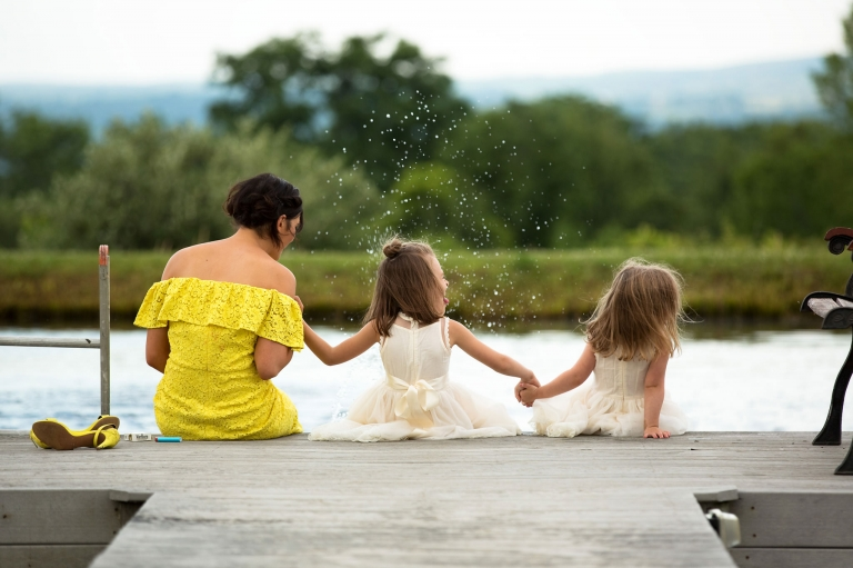 Photo from behind of one adult guest and two young girl looking down a pond deck, shoes off and splashing.