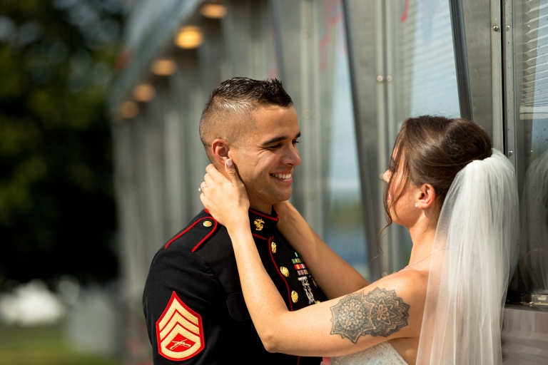 Photo of a bride pulling her marine husband in for a kiss.