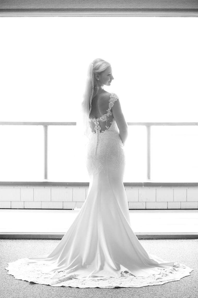 Photo of a bride, full body and dress shot, looking over her shoulder backlighted by a large balcony door.