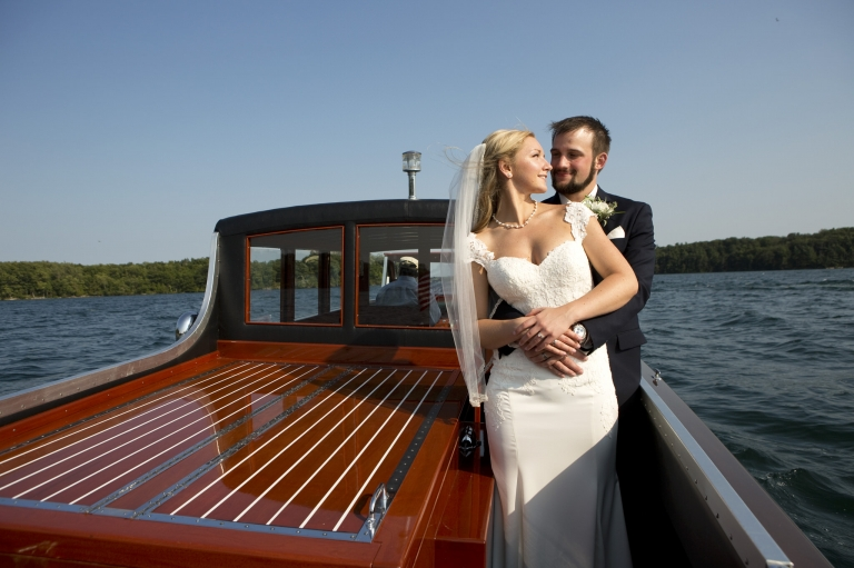 Photo of a groom holding his bride from behind with arms wrapped upon her waist. Setting is on a antique boat ride on the St. Lawrence river.