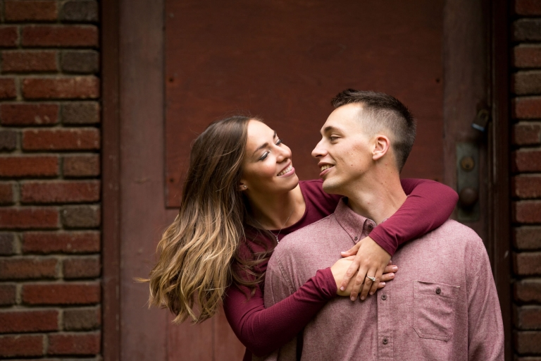 A photo of an engaged couple with her arms wrapped around him from behind.