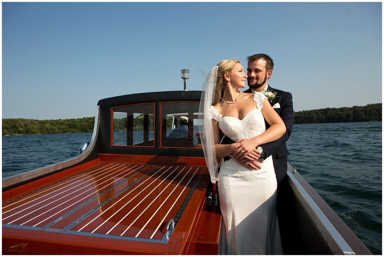 A  photo of a bride and groom embracing while looking into each other's eyes. Setting: vintage boat. Blue skies and water.