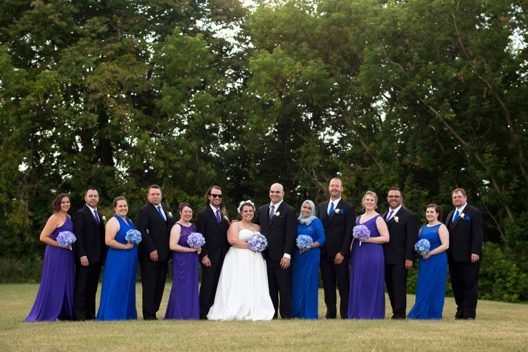 Photo of a bride and groom with their wedding party.