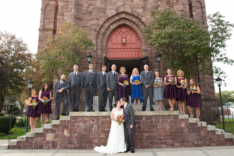 Photo of a bride and groom with their family and wedding party.